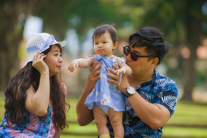 Young happy loving Asian Korean parents couple enjoying together sweet daughter baby girl sitting on grass at green city park in stock image