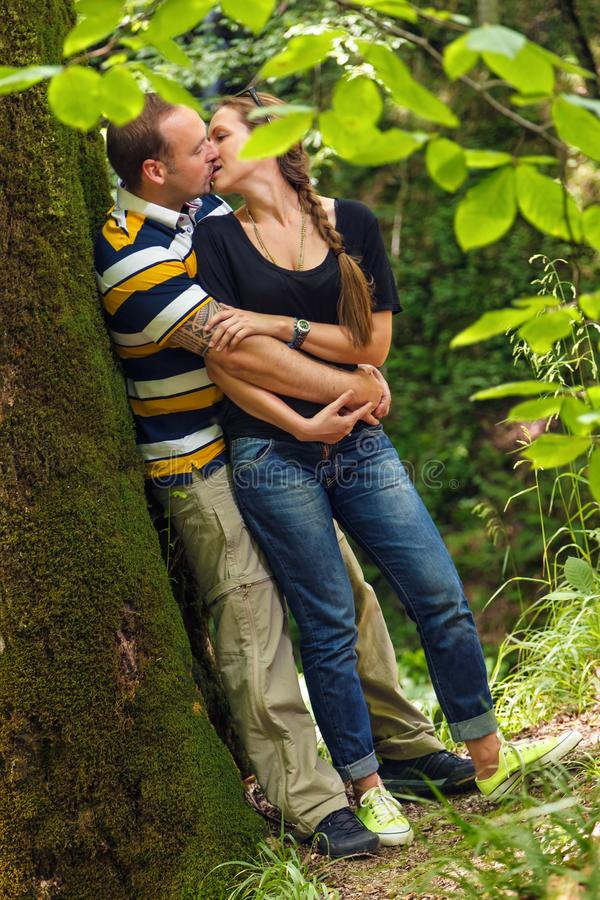 Young happy loving Caucasian couple embracing and kissing in summer forest royalty free stock photography