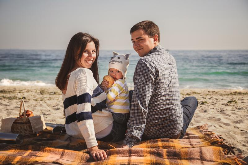 Young happy loving family with small child, enjoying time at beach sitting and hugging near ocean, happy lifestyle family concept royalty free stock photo