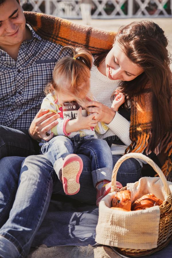Young happy loving family with small child at picnic, enjoying time at beach sitting and hugging near ocean royalty free stock image