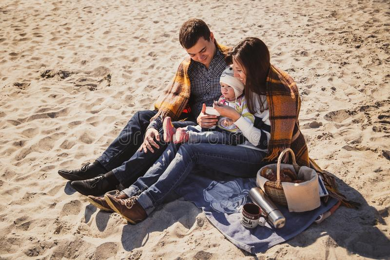 Young happy loving family with small child at picnic, enjoying time at beach sitting and hugging near ocean, happy lifestyle famil stock photos