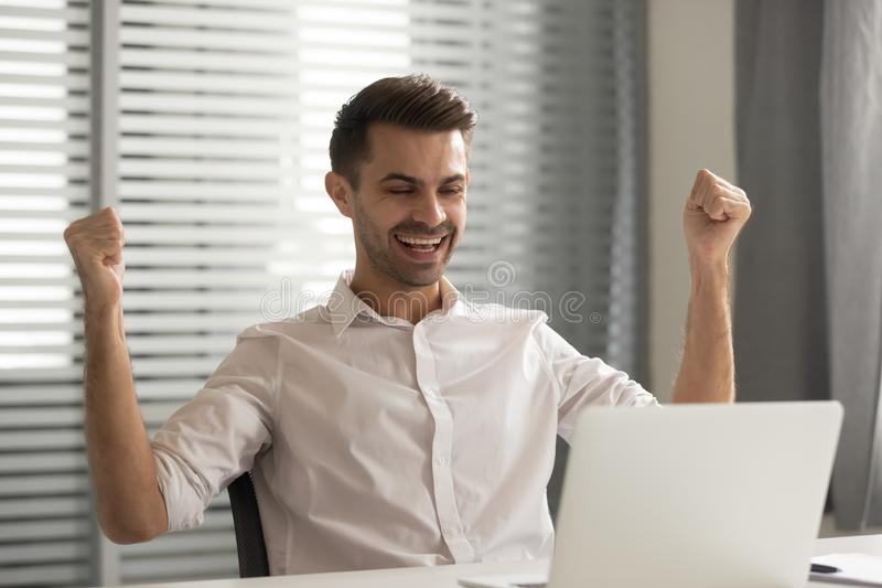 Young happy male employee celebrating job promotion at office. royalty free stock photos