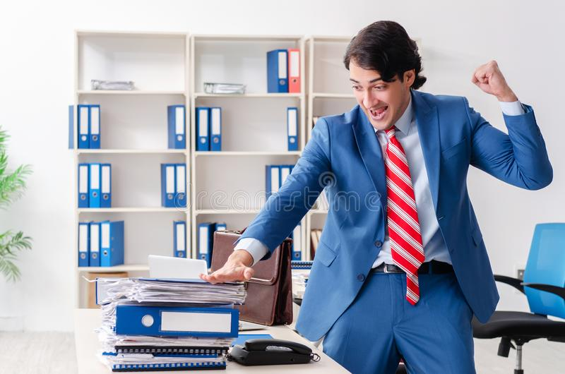 Young happy male employee in the office stock photography
