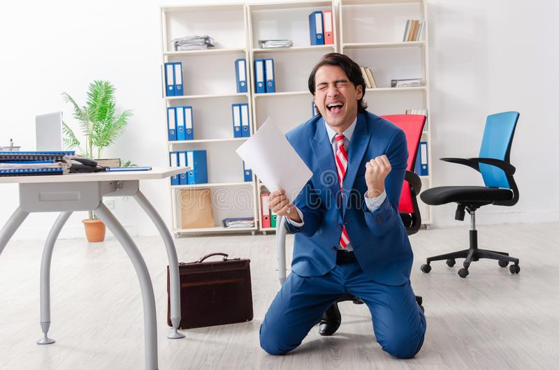 The young happy male employee in the office stock photo