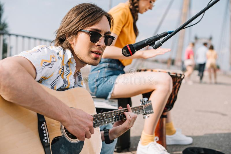 Young and happy male guitarist and female singer stock photo