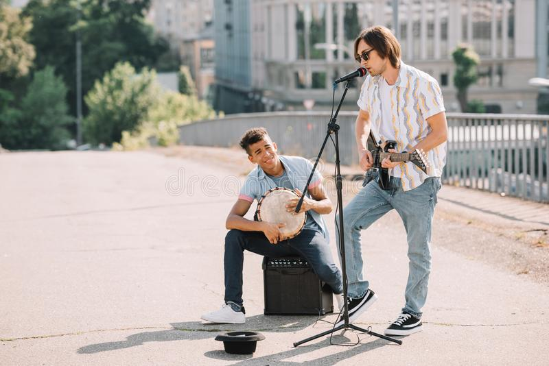 Young and happy male street musicians playing guitar and djembe. In city stock images