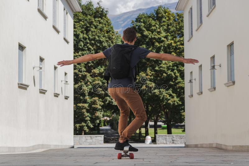 Young happy man with backpack using longboard for going to school after summer holidays stock photo