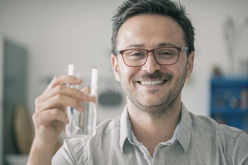 Young happy man drinking water in kitchen stock photography
