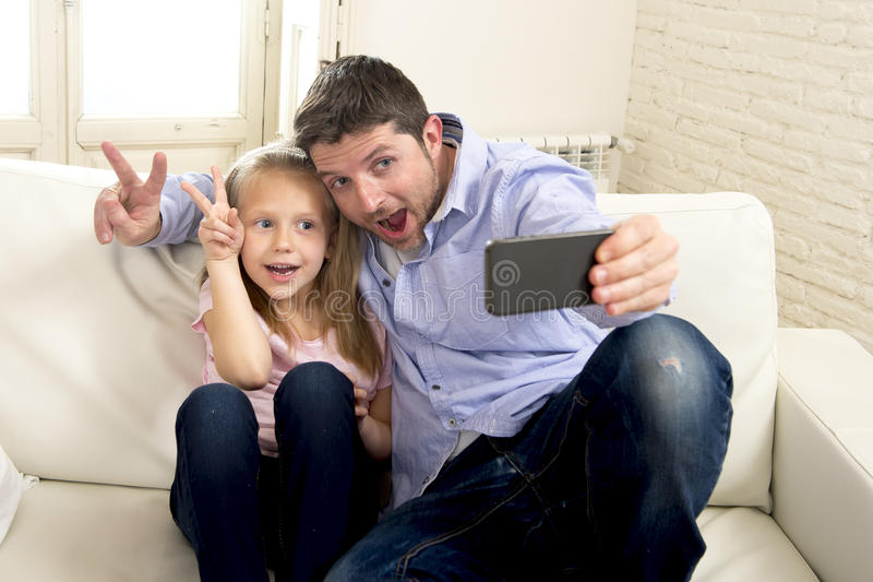 Young happy man having fun with his little cute blond daughter taking selfie photo with mobile phone stock images