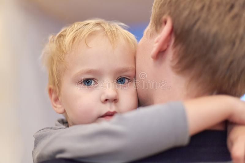 Young happy man holding his cute son. Baby boy embraces the male neck. Serious little kid with blue eyes napping in parent arms. S stock photo