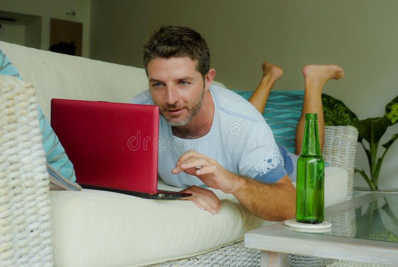 Young happy man lying at home sofa couch relaxed using internet on laptop computer watching online movie or working as independent. Lifestyle indoors portrait of stock photography