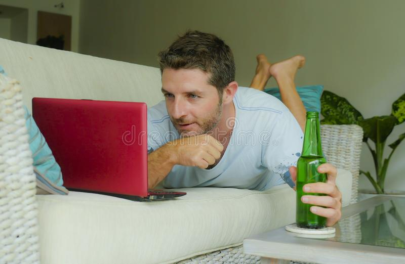 Young happy man lying at home sofa couch relaxed using internet on laptop computer watching online movie or working as independent. Lifestyle indoors portrait of royalty free stock photography