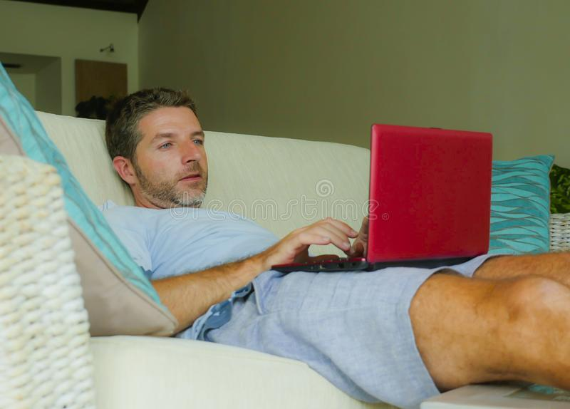 Young happy man lying at home sofa couch relaxed using internet on laptop computer watching online movie or working as independent. Lifestyle indoors portrait of royalty free stock photos