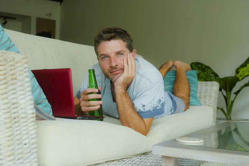 Young happy man lying at home sofa couch relaxed using internet on laptop computer watching online movie or working as independent. Lifestyle indoors portrait of stock image