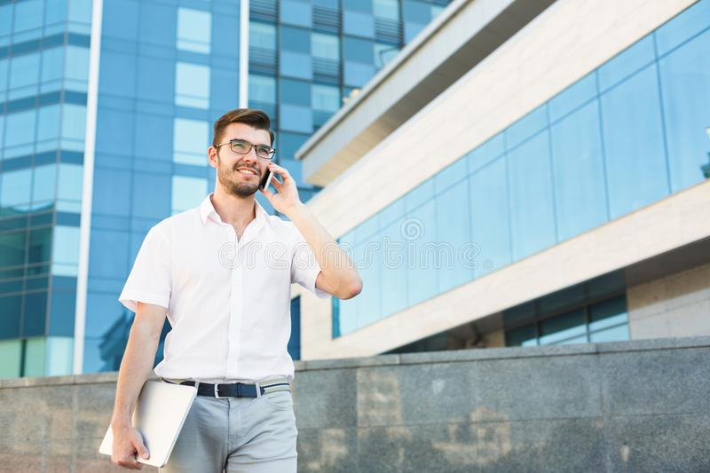 Young happy man making a call and holding tablet outside royalty free stock image