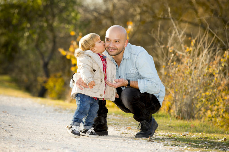 Young happy man playing with excited little cute son the child kissing his father royalty free stock photography