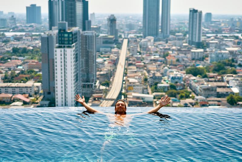 Young happy man relax on the edge of swimming pool in roof top of hotel. Summer vacation concept royalty free stock image