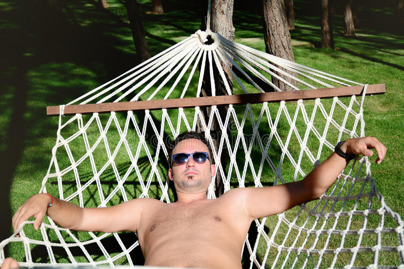 Young happy man Relaxing In Hammock in a garden with sea view royalty free stock photo