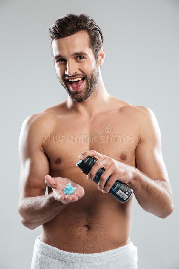 Young happy man standing isolated holding shaving foam. Image of young happy man standing isolated over grey background holding shaving foam. Looking at camera stock images