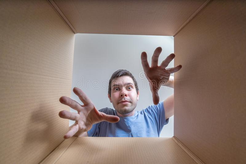 Young happy man is stretching hands. View from inside cardboard box royalty free stock photo