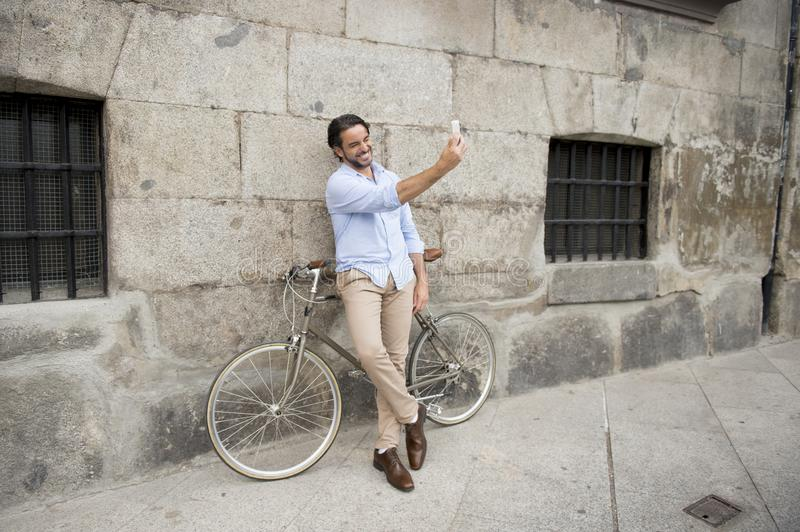 Young happy man taking selfie with mobile phone on retro cool vintage bike. Young happy attractive hispanic man in casual trendy clothes smiling cheerful using stock image