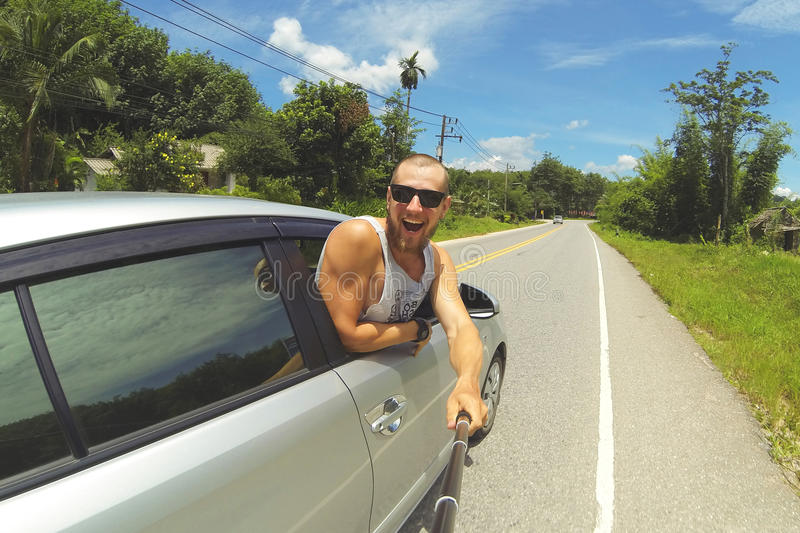 Young Happy Man Taking Selfie Picture with Smartphone on Monopod Stick. Hipster Making Road Trip Photo From Car Window. Young Happy Man Taking Selfie Picture stock photography