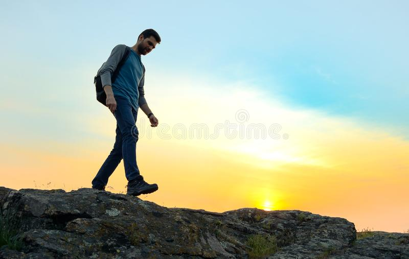 Young Happy Man Traveler Hiking with Backpack on the Rocky Trail at Warm Summer Sunset. Travel and Adventure Concept stock images