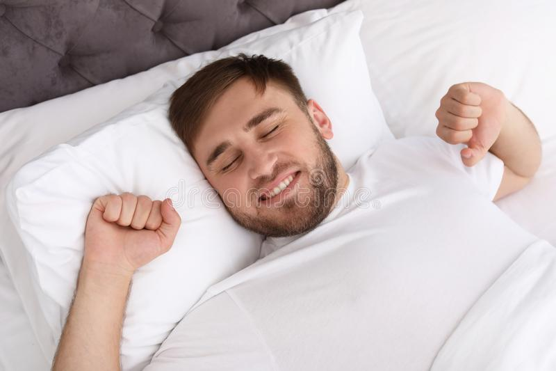 Young happy man waking up after sleeping in bed stock photo