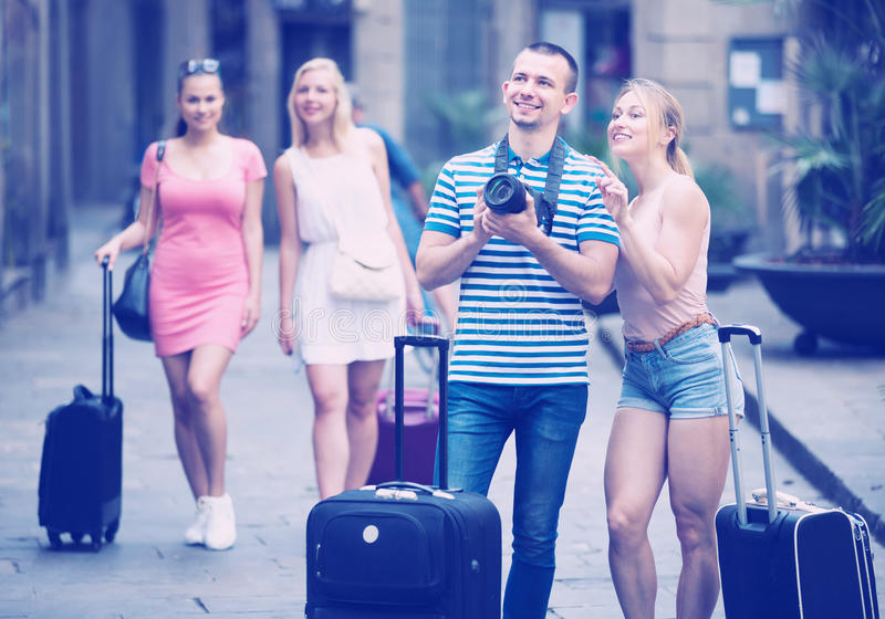 Young happy man and woman tourists holding camera stock images