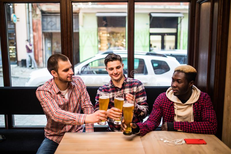 Young happy multiracial men friends drinking beer and talking in pub stock photos