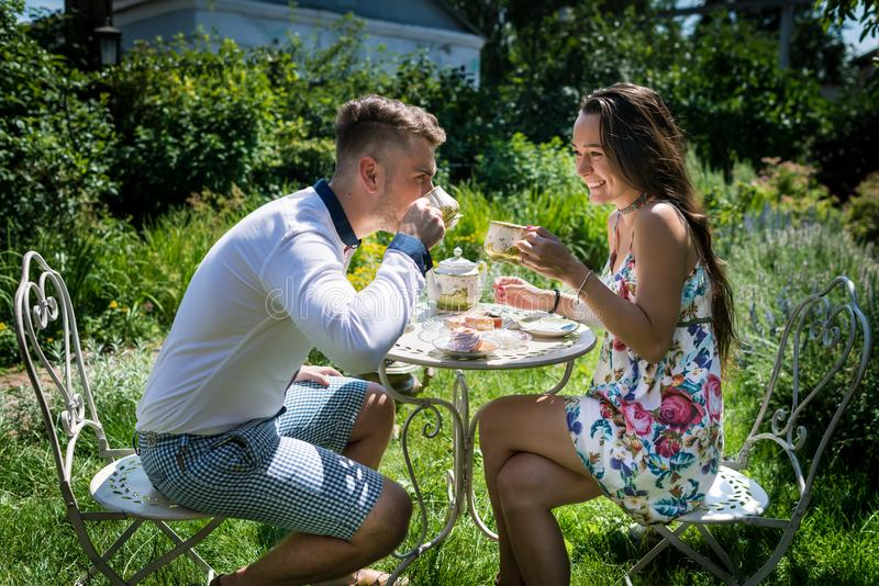 Young happy man sits with girlfriend and drinks tea at the table with sweets stock photos