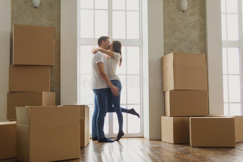 Young happy millennial couple students move into their first new owners home. Simple white background of urban apartment. Young couple very happy and excited stock photo
