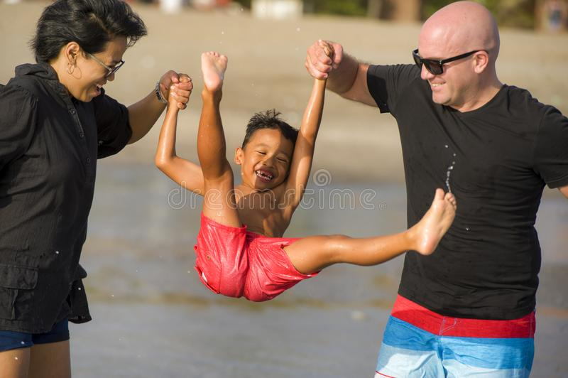 Young happy mixed ethnicity couple Caucasian man and Asian Indonesian woman playing at tropical beach with little son the parents stock image