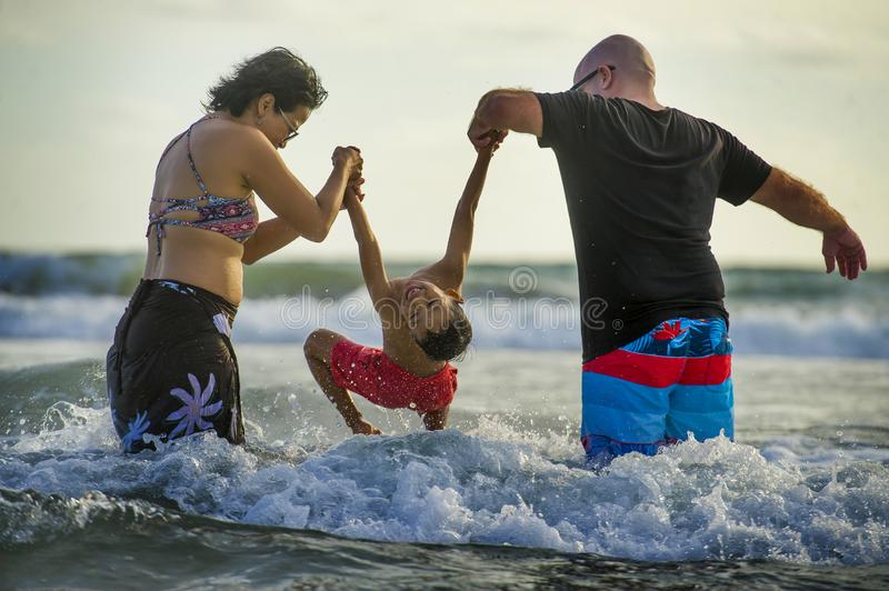 Young happy mixed ethnicity couple Caucasian man and Asian Indonesian woman playing at tropical beach with little son the parents royalty free stock photography