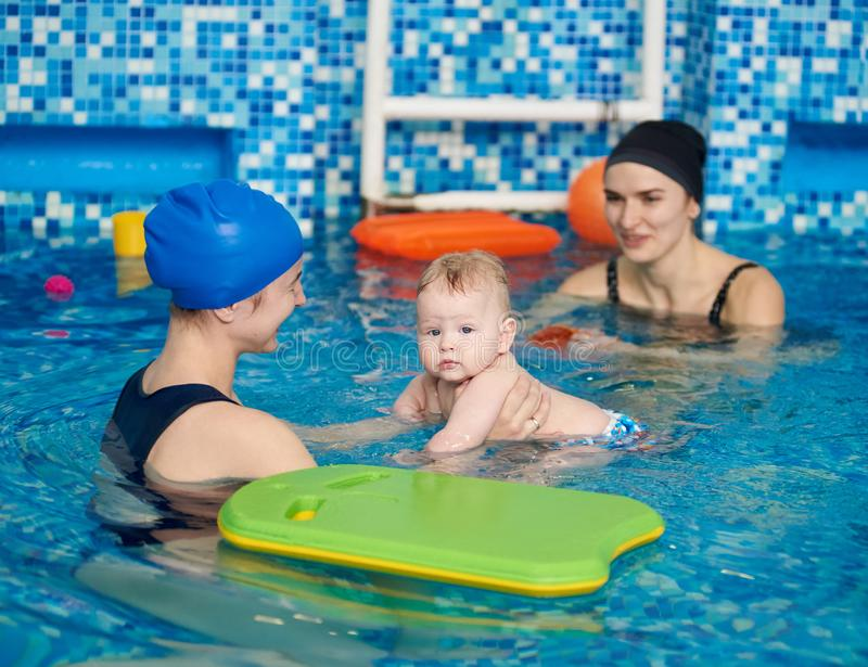 Young happy mother and baby enjoying floating looking aside at paddling swimming lesson with trainer in swimming pool royalty free stock photo