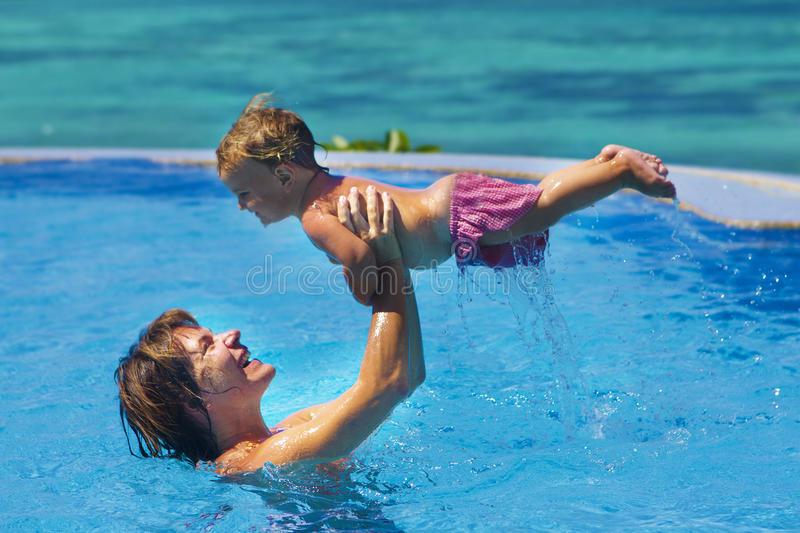 Young happy mother and baby. Enjoying vacation in swimming pool on tropical sea background royalty free stock photos