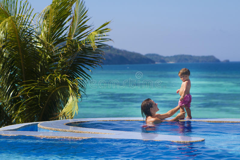 Young happy mother and baby enjoying vacations. Young happy mother and baby enjoying vacation in swimming pool on tropical sea background stock photo