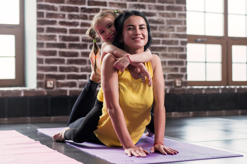 Young happy mother doing stretching exercise on mat while her smiling daughter hugging her in sports club stock photography