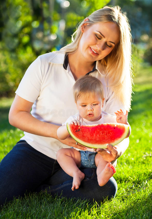 Young happy mother and her baby daughter eating watermelon. Outdoors stock photography