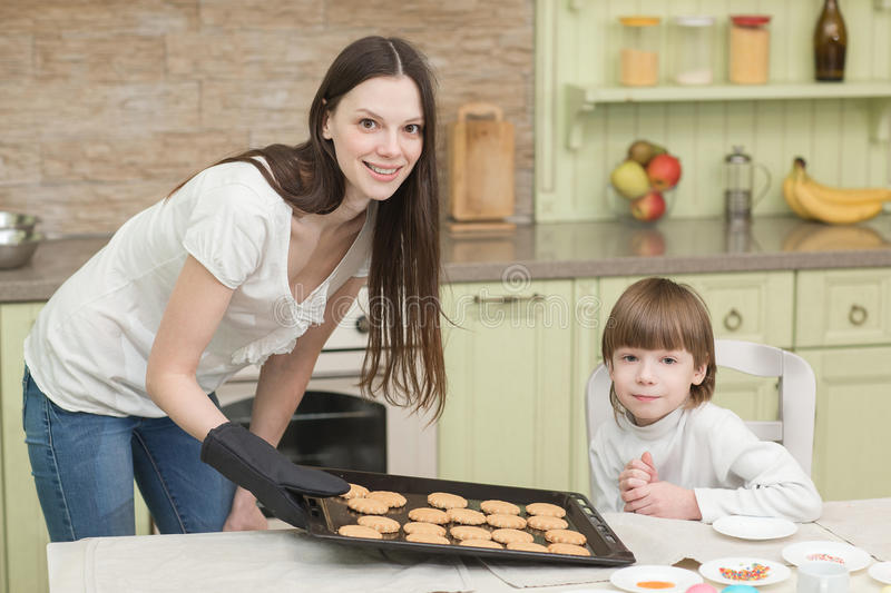 Young happy mother and her child testing cookies stock photo