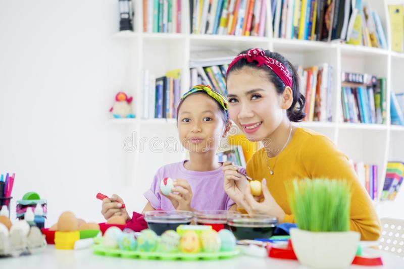 Happy mother paints eggs with her daughter royalty free stock photos
