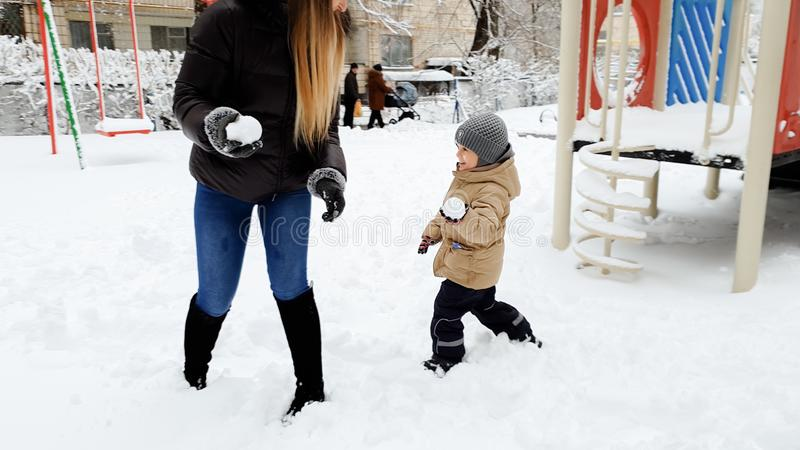 Image of young happy mother playind in snow balls with her cute son in jacket and hat on the playground in the Park royalty free stock photos