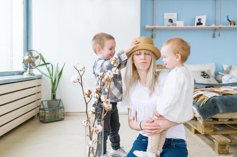 Young and happy mother in a straw hat hugs her two beautiful children. Sitting in children room at home stock photo