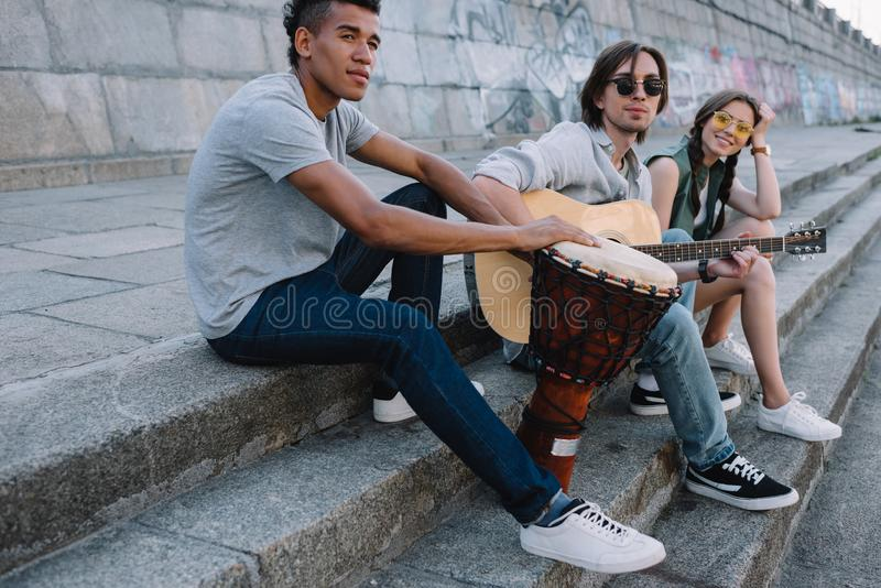 Young and happy multiracial street musicians band sitting with instruments. In city stock photos