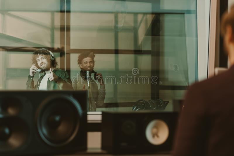 Young happy musicians recording song behind glass at studio and showing. Thumbs up stock photo