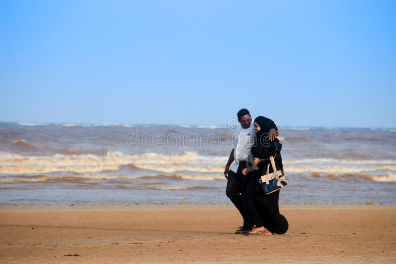 A young happy Muslim black couple are walking along the coast of the Indian Ocean royalty free stock image