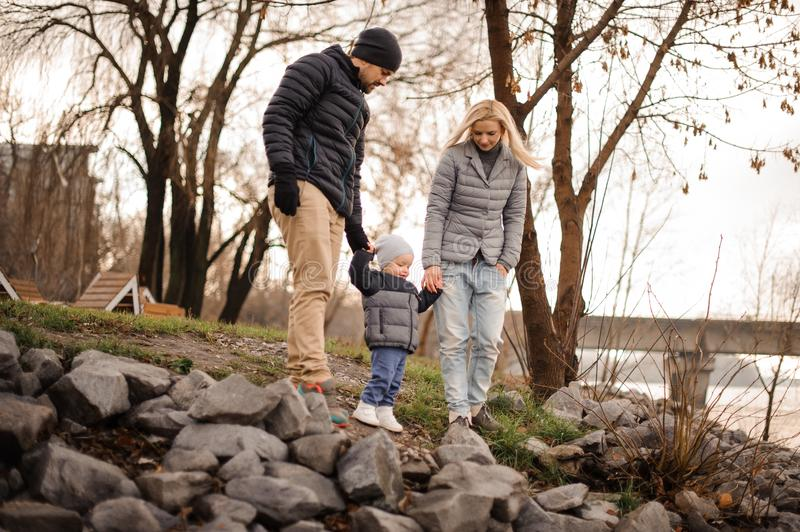 Young and happy parents walking with a little son stock image