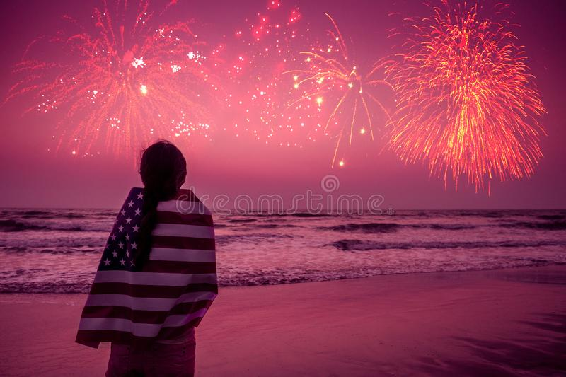 Young happy patriot girl holding the American flag on the 4th of July and looks at the salute stock photography