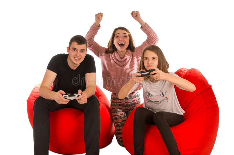 Young happy people are enthusiastic about playing video games while sitting on red beanbag chairs royalty free stock photos