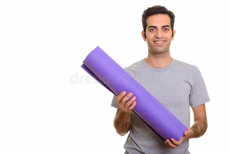 Young happy Persian man holding yoga mat ready for gym royalty free stock photo